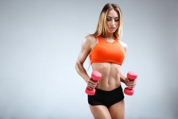Slim female fitness model in the white studio