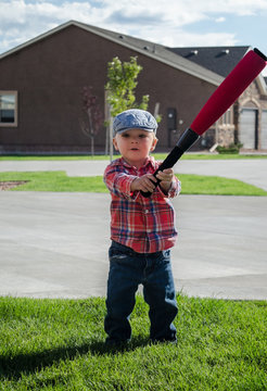 Toddler boy playing baseball with a white wiffle ball and red bat. Wearing blue motoring cap, red plaid shirt and blue jeans on grass on sunny cloudy day.