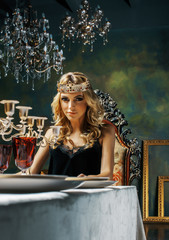 young blond woman wearing crown in fairy luxury interior with em