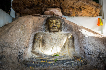 Old buddha image on the rock.
