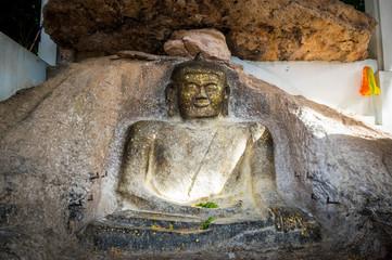 Old buddha image on the rock.