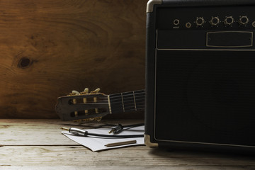 Guitar amplifier and guitar on wood table, light and shadow