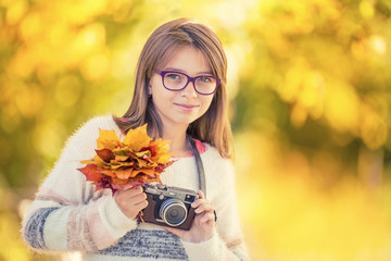 Autumn time. The teenage attractive cute young girl with autumn bouquet and retro camera. Young girl photographer autumn  season..