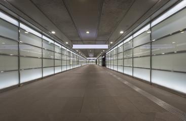 Empty corridor at night with glass illuminated walls