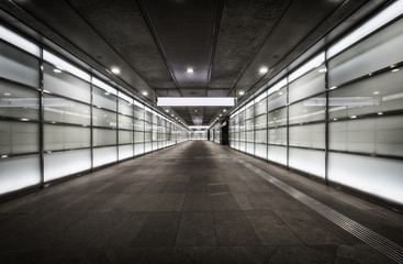Empty corridor at night with glass illuminated walls