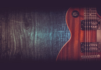 Part of the orange electric guitar on wooden background. A place for writing of the text.