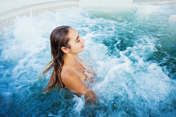 tourist woman relaxing in a thermal hotspring or jacuzzi bath