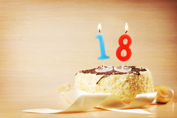 Birthday cake with burning candle as a number eighteen. Focus on the candle