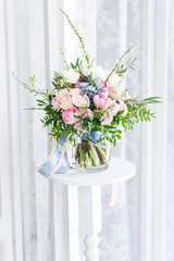 a cute bouquet of massive pink flowers with green brunches standing on a high white stand, lace white curtains behind