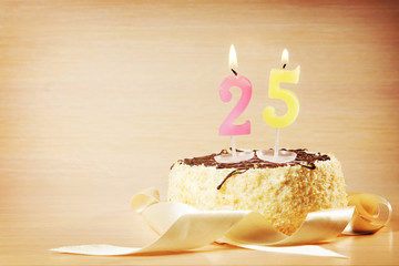 Birthday cake with burning candle as a number twenty five. Focus on the candle
