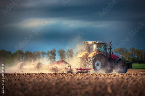 Fototapete Farmer in tractor preparing land with seedbed cultivator