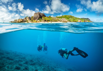 Spoed Fotobehang Duiken Divers below the surface in Seychelles