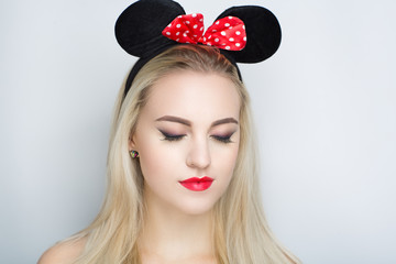 The girl with funny black round mouse ears and red bow with white spots, sexy play boy show. Young beautiful lady fashionable hairdo and professional makeup. perfect shape of lips shiny color lipstick