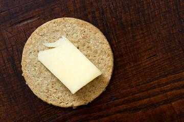 Single Scottish oatcake with a slice of yellow cheese.