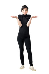 Funny confused clueless young woman in black turtleneck and pants shrugging shoulders. Full body length portrait isolated over white studio background.