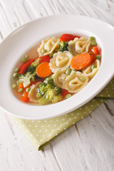 tortellini soup with broccoli, peas, carrot and pepper close-up. vertical