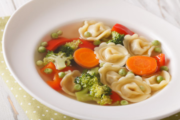 Italian soup with tortellini and vegetables closeup at the plate. horizontal