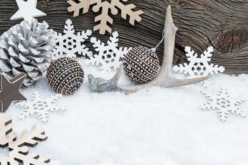 Geweih mit Weihnachtskugeln und Sternen im Schnee