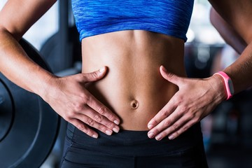 Midsection of athlete touching belly in gym
