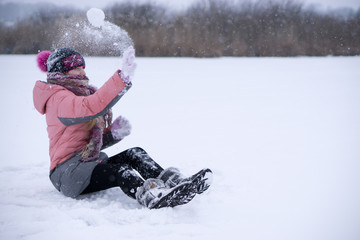 closeup shot of a young teenage girl sit alone on a frozen ground lake in snow and throwing snowball her face head wrapped in scarf.