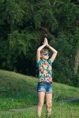 one young teenage girl in mirrored glasses goggles standing on hills palms tight hand up close together above her head like praying or doing yoga at the park in flowered t-shirt and jeans shorts with