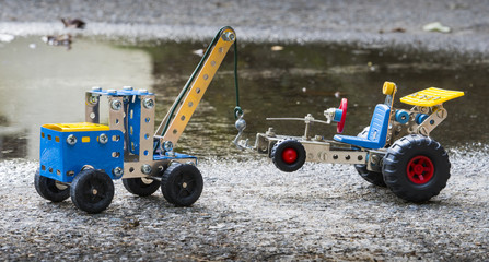 Toy tow truck lifts car, both built with small pieces of metal and plastic. Roadside assistance concept.