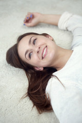 young woman lying on carpet and smiles