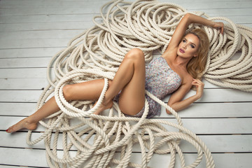 Sexy blond woman lying on white rope
