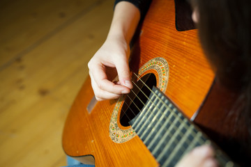 Young woman playing on the old wood guitar and enjoying nice tim
