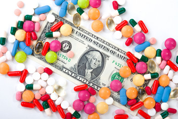 Pills and tablets on white background with dollar bill in vivid