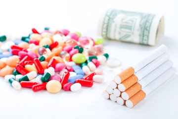 Cigarettes, colorful pills and tablets with dollar bill on a white background