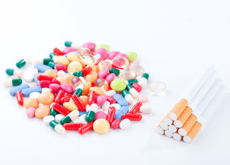 Cigarettes colorful pills and tablets on a white background