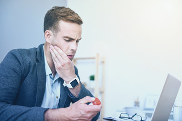Good looking dissatisfied man having headache by working place.