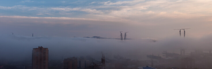 Vladivostok cityscape. Foggy day. Construction of the bridge.