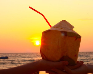 hands hold coconut with straw