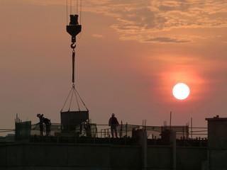 Ouvriers sur un chantier du bâtiment avec soleil couchant