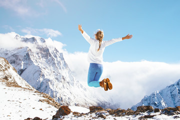 Woman jumping on mountain in winter