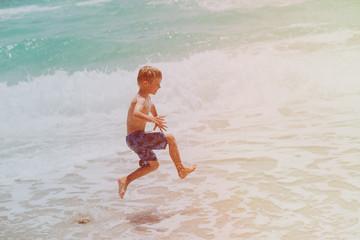 happy little boy enjoy play with waves on beach