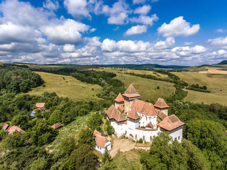 Viscri fortified Chruch in the middle of Transylvania, Romania. Aerial view from drone. Important tourist attraction.