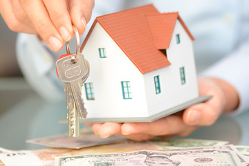 Buying a house concept with woman hands holding a model house and keys