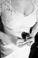 Black and white picture of a bide holding in her arms a poppy bu