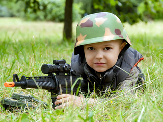Boy in army camouflage with toy gun outdoor