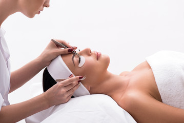 Beautiful young woman during eyelash extension