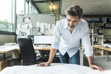 Architect working on ground plan in office