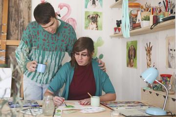 Artist painting in her studio while her boyfriend watching her