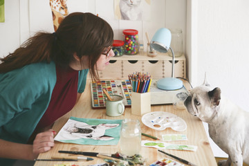 Artist watching French bulldog in her studio