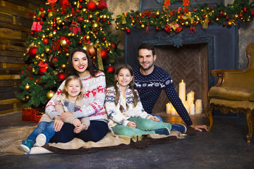 Young family near fireplace celebrating Christmas