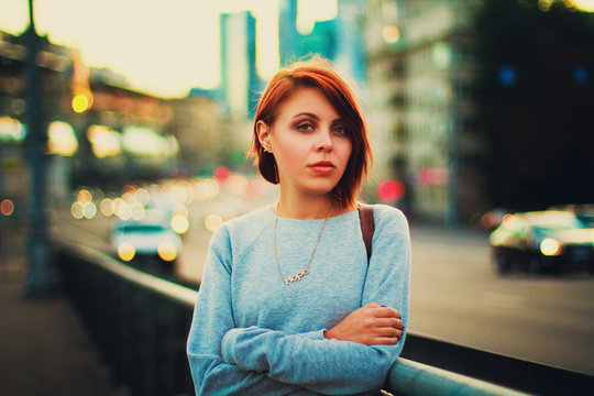 Red-haired girl on the background of a megacity