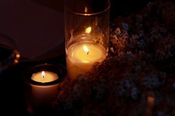 Glasses with candles stand in the flower wreath