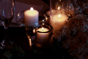 White candles burn in wreath of little white flowers